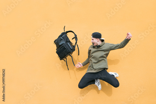 Obraz Street young man jumping with a backpack on the background of an orange wall - fototapety do salonu
