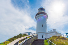 View Over Cape Byron Lighthouse, The Most Easterly Point On The Australian Mainland With Green Turquoise Water Waves In Byron Bay, Australia. Intentional Lens Flare Effect.