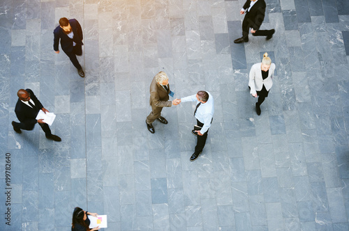 Businessmen shaking hands in crowded office hall