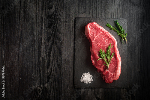 raw strip loin steak on black wooden background