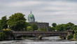 View of Dome of Galway city Cathedral and historic stone bridge crossing in the distance.