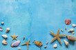 Seashells with copy space on a blue concrete or stone background. Sea summer vacation background. Top view flat lay.