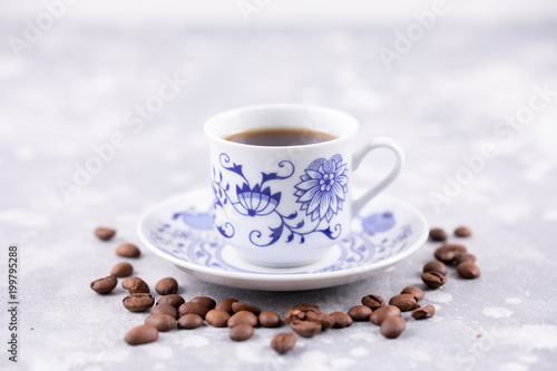 Foto op Canvas Cafe A beautiful porcelain coffee cup with hot black coffee. Coffee beans scattered around the background. Vintage china. A white-blue cup on a gray background.