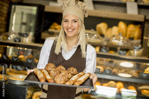 In de dag Bakkerij Female bakery posing with various types of pastries and breads in the bakery