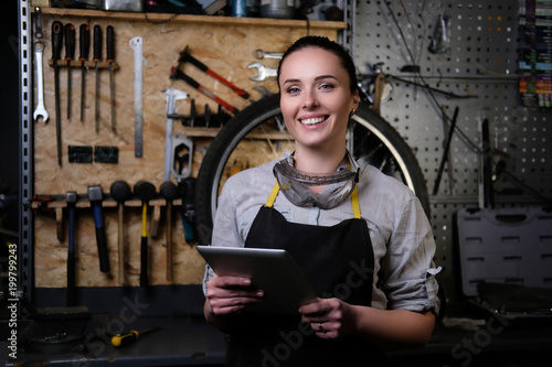 Juliste  Portrait of a beautiful brunette female wearing working clothes, apron and goggles, holds a tablet computer in a workshop