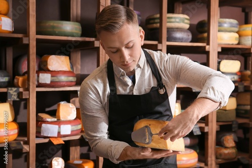 Pinturas sobre lienzo  Young worker slicing cheese in shop