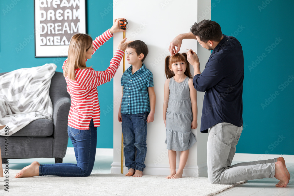 Fototapety, obrazy: Parents measuring height of their children at home