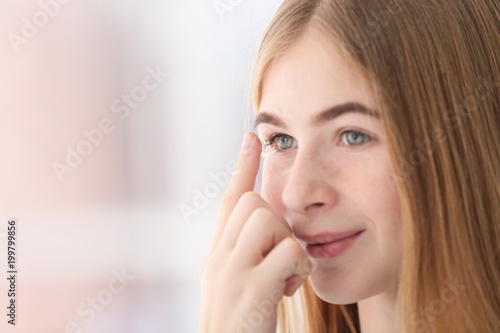 Fotografía  Teenage girl putting contact lens in her eye on blurred background