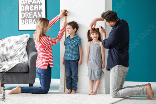 Fotomural  Parents measuring height of their children at home