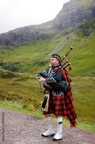 Photo Piper in traditional Scottish outfit plays on bagpipes in Scottish Highlands