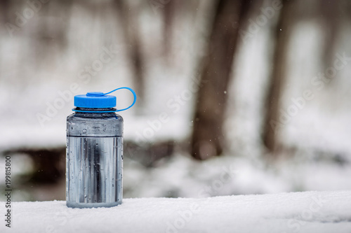 bottle on wood with winter scene background. Bushcraft concept.