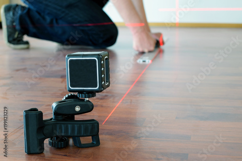 Man using cross-line laser to mark the floor Canvas-taulu