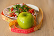 healthy eating, dieting, slimming and weigh loss concept - close up of green apple, measuring tape and salad.