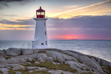 Sunset behind the lighthouse at Peggy's Cove near Halifax, Nova Scotia Canada.