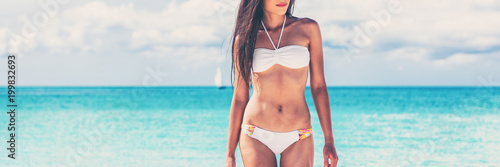 Fototapeta Summer bikini body weight loss woman with toned abs and slim stomach on beach background
