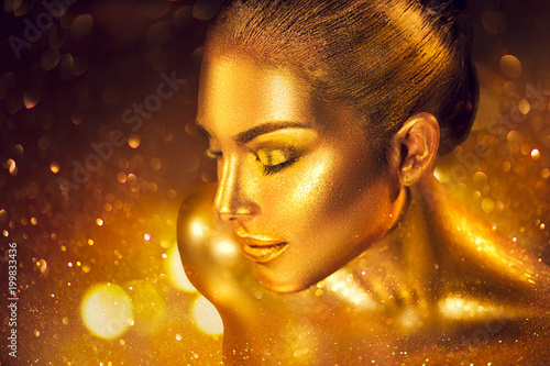 Fashion art golden skin woman portrait closeup. Gold, jewelry, accessories. Model girl with golden glamour shiny makeup