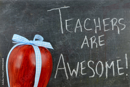 Teacher appreciation image of a red apple tied up with a cute blue ribbon in fro Wallpaper Mural