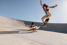 Female Skaters Doing Stunts At...