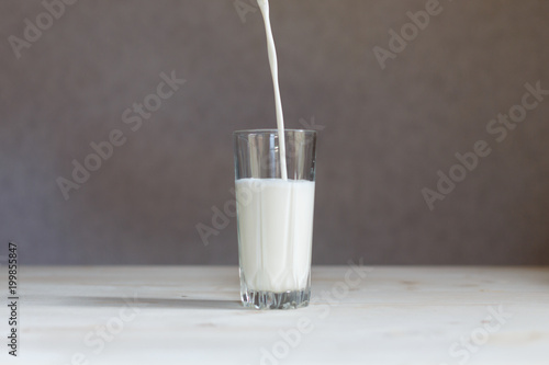 Stream milkshake poured into a glass on wooden table. Pouring milk from bottle into glass. Isolated wooden background.