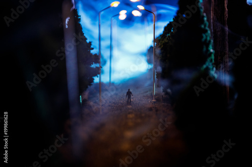 City at night in dense fog. Thick smog on a dark street. Silhouettes of man on road. Table decoration. Selective focus
