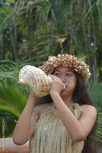 Polynesian Cook Islander  woman blowing conch shell in Rarotonga Cook Islands Canvas Print