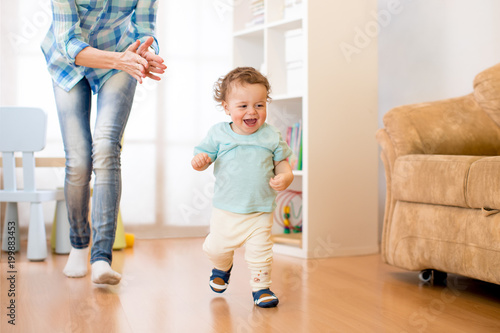 Baby toddler have a fun running in living room with his mother Canvas Print