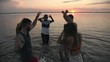 Tilt down of ecstatic group of young people laughing and dancing in lake at sunset on summer evening