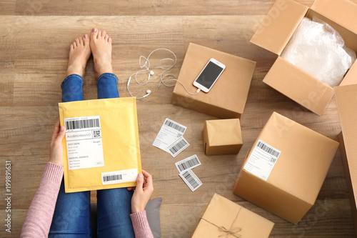 Obraz Woman with padded envelope and parcels on floor - fototapety do salonu