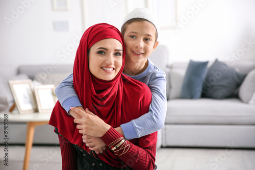 Muslim woman in traditional clothes with her son at home