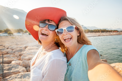 Photo An attractive middle-aged woman with her adult daughter doing selfie on the beac