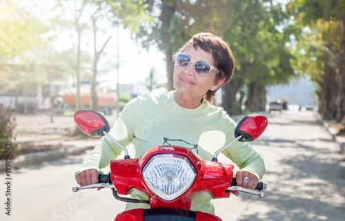 Fotografia, Obraz  Beautiful mature stylish woman on motobike on a summer day, active pension and t