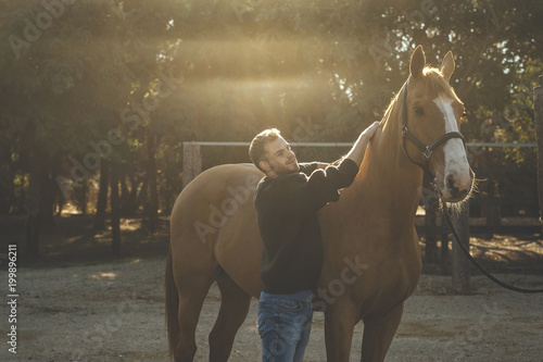 Horse man looking with affection to his brown horse in the field at sunrise and lens flare