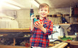 children, carpentry, profession and people concept - happy little boy with drill at workshop