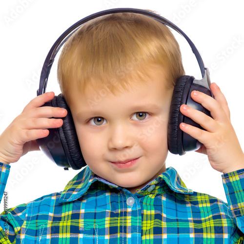 Fotografía  A little boy in big stereo headphones.
