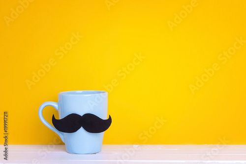 Blue mug with a mustache on yellow background. Copy space. Fathers day holiday.
