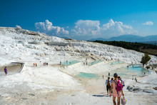 Tourists Visiting The Limestone, Travertine, Rocks Pamukkale In Turkey On A Sunny Day.