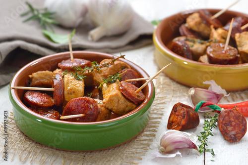 Foto auf AluDibond Bar Spanische Pinchos: Geschmorte Schweinefilet-Stückchen mit angebratener scharfer Chorizo Paprikasalami serviert – Spanish snack: Braised pork fillet with fried slices of chorizo paprika sausage
