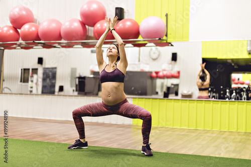Fotografering  Pregnant woman is doing exercises at the gym