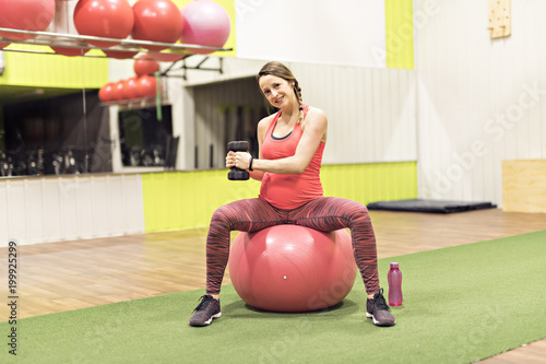 Pregnant woman is doing exercises at the gym Canvas Print