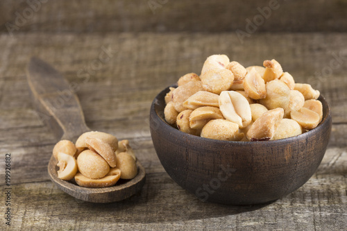 Toasted peanuts on wooden background - Arachis hypogaea Canvas Print
