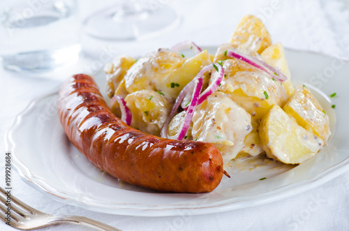 Fotografie, Obraz  grilled sausage with classical potato salad with mayonnaise dressing on white ba