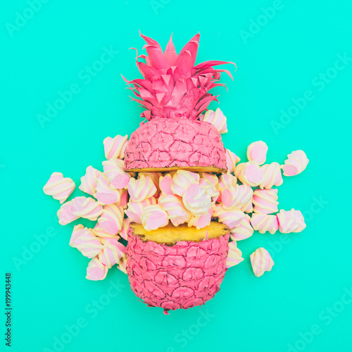 Fotografia, Obraz  two painted in pink color halfs of the pineapple of which fall marshmallow on turquoise background
