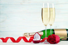 Champagne Bottle With Glasses, Red Rose And Silver Ring On Wooden Table