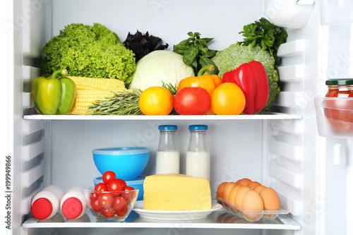 Open fridge full of vegetables and cheese with bottles of milk