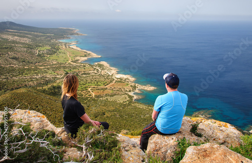 man and woman sitting on rock and looking at the Mediterranean Sea