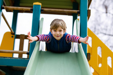 Happy Blond Kid Boy Having Fun And Sliding On Outdoor Playground