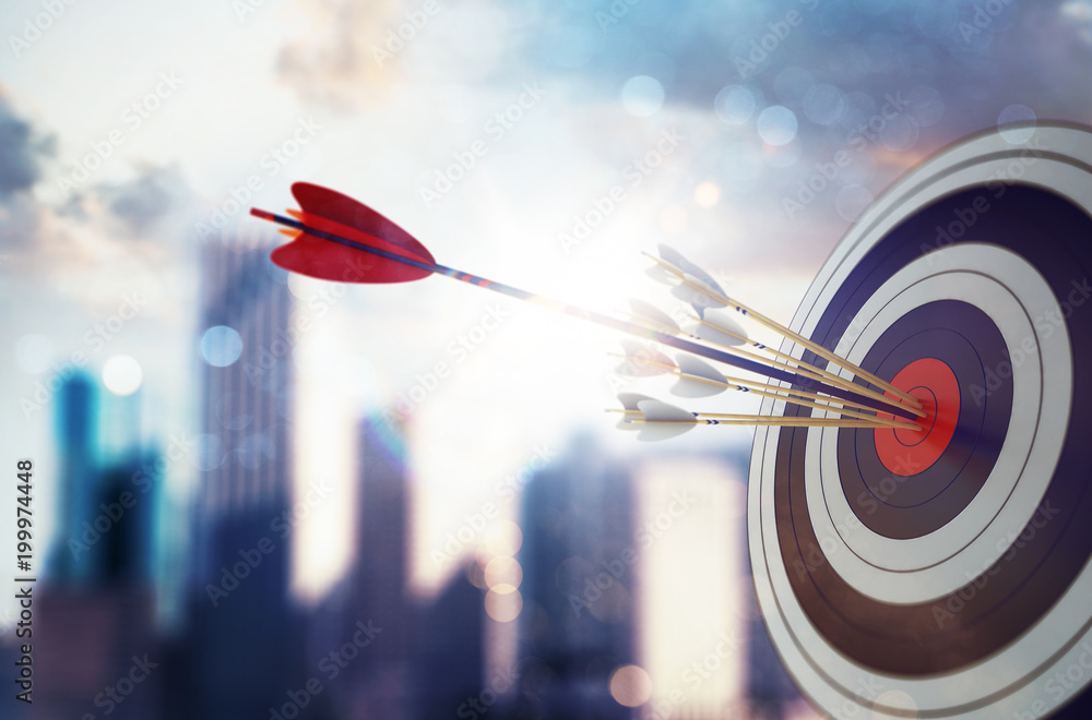 Fototapeta Arrow hit the center of target with modern skyscraper background. Business target achievement concept. 3D Rendering