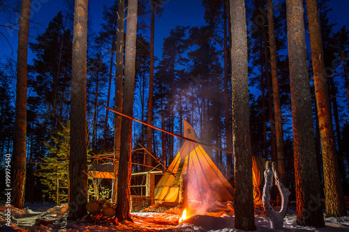 The wigwam in the evening forest Fotobehang