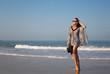 Beautiful, elegant girl, model strolls along the seashore. Lifestyle, style, fashion, beauty.