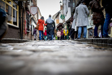 Low Down Shot Of People And Couple Walking Holding Hands Down A Old Traditional Cobbled English Street Whilst Browsing In Shops On Retail Therapy Day